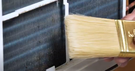 Cleaning the air conditioner coils with a paint brush