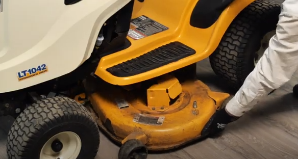 Removing the mower deck from the lawn tractor to access important parts.